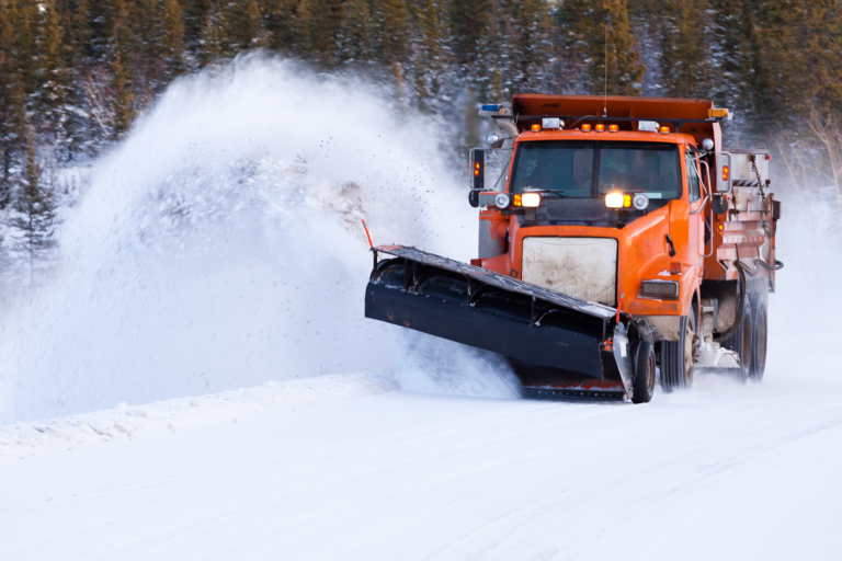 Snow plow operating on a road filled with snow and ice that uses Cypress VUE